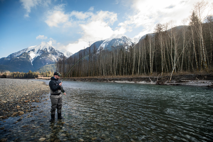 Fly fisherman hooked up on bull trout wearing simms waders and , Mount blackwall in background