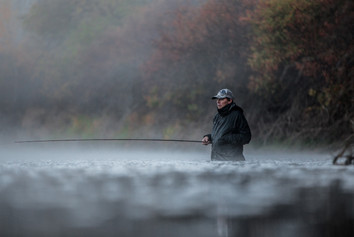 Steelhead fisherman sits idle for a tug in washington with fall colors and fog rolling down river