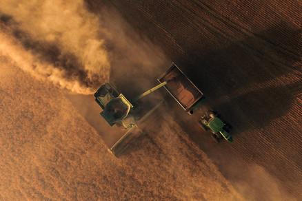 John Deere Combine dumping wheat in Brent Grain Cart