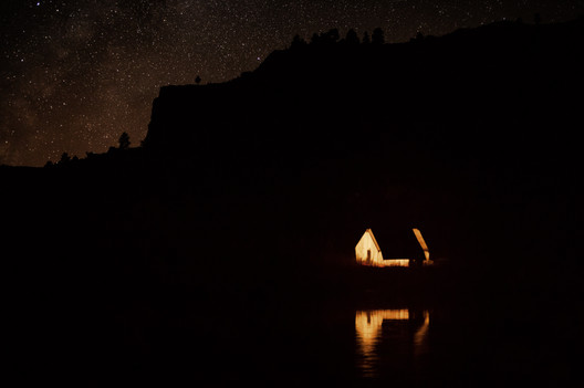 Elk camp in Montanas missouri river breaks a wall tent and its reflection on the river is lit up by a lantern and the stars