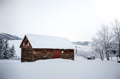 An old barn with a red door stands out strong and well built after a heavy winter storm in Central Montana