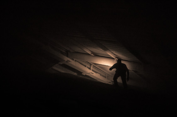 Wheat farmer with flashlight walks up pile of wheat in dry storage bin looking for problem with grain delivery system