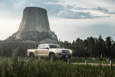 Toyota Tacoma Quicksand Tan TRD Offroad 2018 driving down road at the Devils Tower