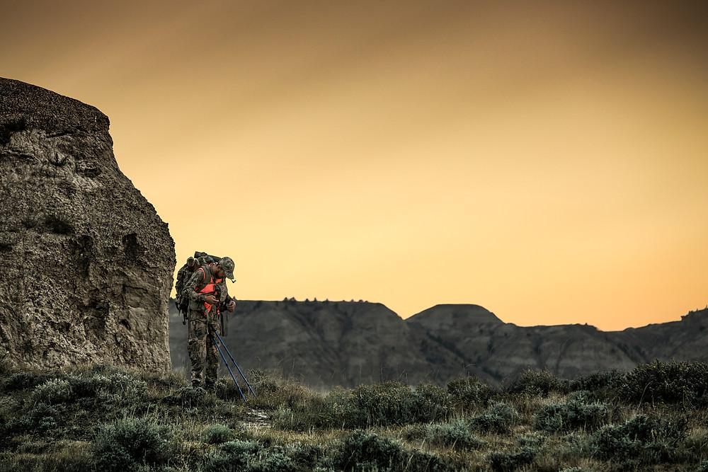 Sheep hunter stands on ridge line in the Missouri river breaks adjusting pack