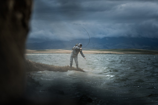 Fly fisherman throwing rod hard into gusting winds on white cap covered lake in Montana