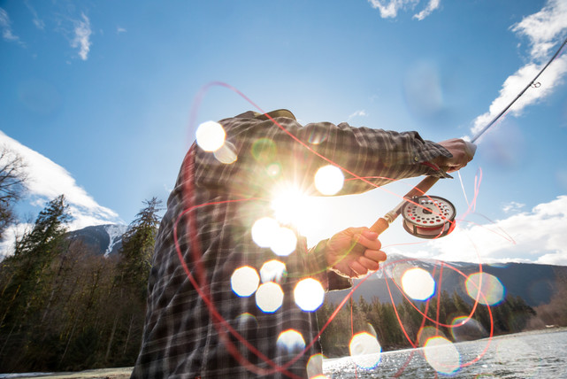 Fly fisherman wearing simms flanel throwing a double handed spey rod with running line flying through guides