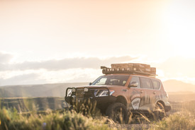 Nissan Armada Mountain Patrol Overland rig with CVT tent, Calmini bumpers, Warn winch, Nitto tires, ARB, and Rhino Rack. Offroad truck parked on ridge with sunset in background