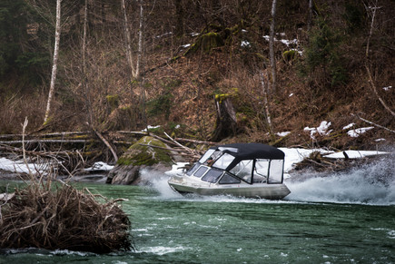 Firefish Pirhana jet boat turning around a narrow channel on a remote river in British Columbia on a fly fishing trip