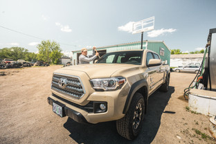 Toyota Tacoma Quicksand Tan TRD Offroad 2018 getting fuel and cleaning the windshield in rural Winnett Montana