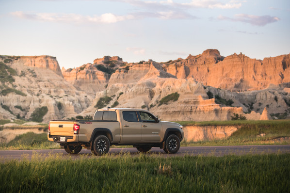 Toyota Tacoma Quicksand Tan TRD Offroad 2018 driving down road in the Badlands National park at sunrise