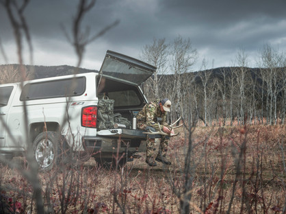 Shed hunter looking over his find of an elk shed on tailgate of chevy silverado shot on hassleblad h6d 50c