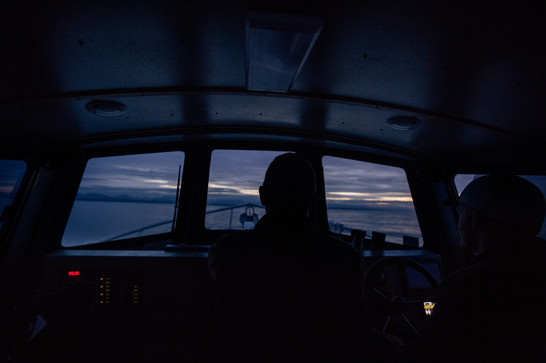 Captain piloting a 27' pilothouse boat around the Vancouver Islands in Canada