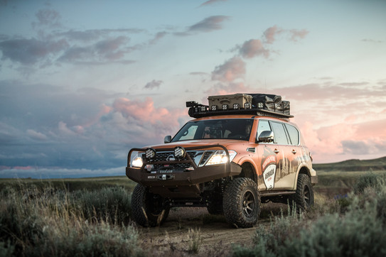 Nissan Armada Mountain Patrol Overland rig with CVT tent, Calmini bumpers, Warn winch, Nitto tires, ARB, and Rhino Rack. Offroad truck driving through sage brush in Wyoming