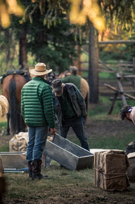Two cowboys planning out the loads for the packstring of mules in the Bob Marshall wilderness area