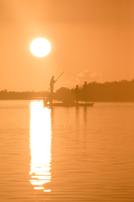Hells Bay flats boat fly fisherman poling into a school of redfish in Mosquito Lagoon Florida with strong sun silhouette