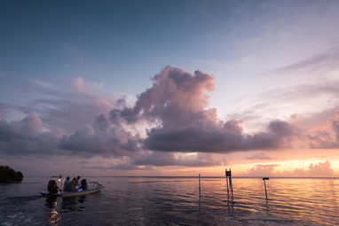 Mosquito Lagoon Florida fly fisherman heading out for the day in Hells Bay flats boat with beautiful pink and purple sunrise