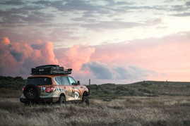 Nissan Armada Mountain Patrol Overland rig with CVT tent, Calmini bumpers, Warn winch, Nitto tires, ARB, and Rhino Rack. Offroad truck driving off into the sunset