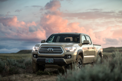 Toyota Tacoma Quicksand Tan TRD Offroad 2018 coming through sage brush on dirt road in North Central Wyoming