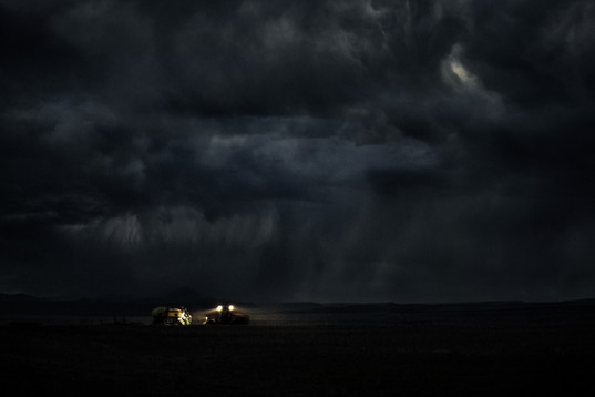 John deere air drill seeding wheat field in Central Montana in the Golden triangle at night right before a storm is about to hit