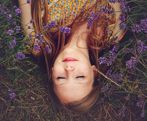 woman in yellow and teal top sleeping beside lavenders_edited.jpg