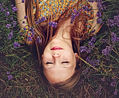 woman in yellow and teal top sleeping beside lavenders_edited.jpg