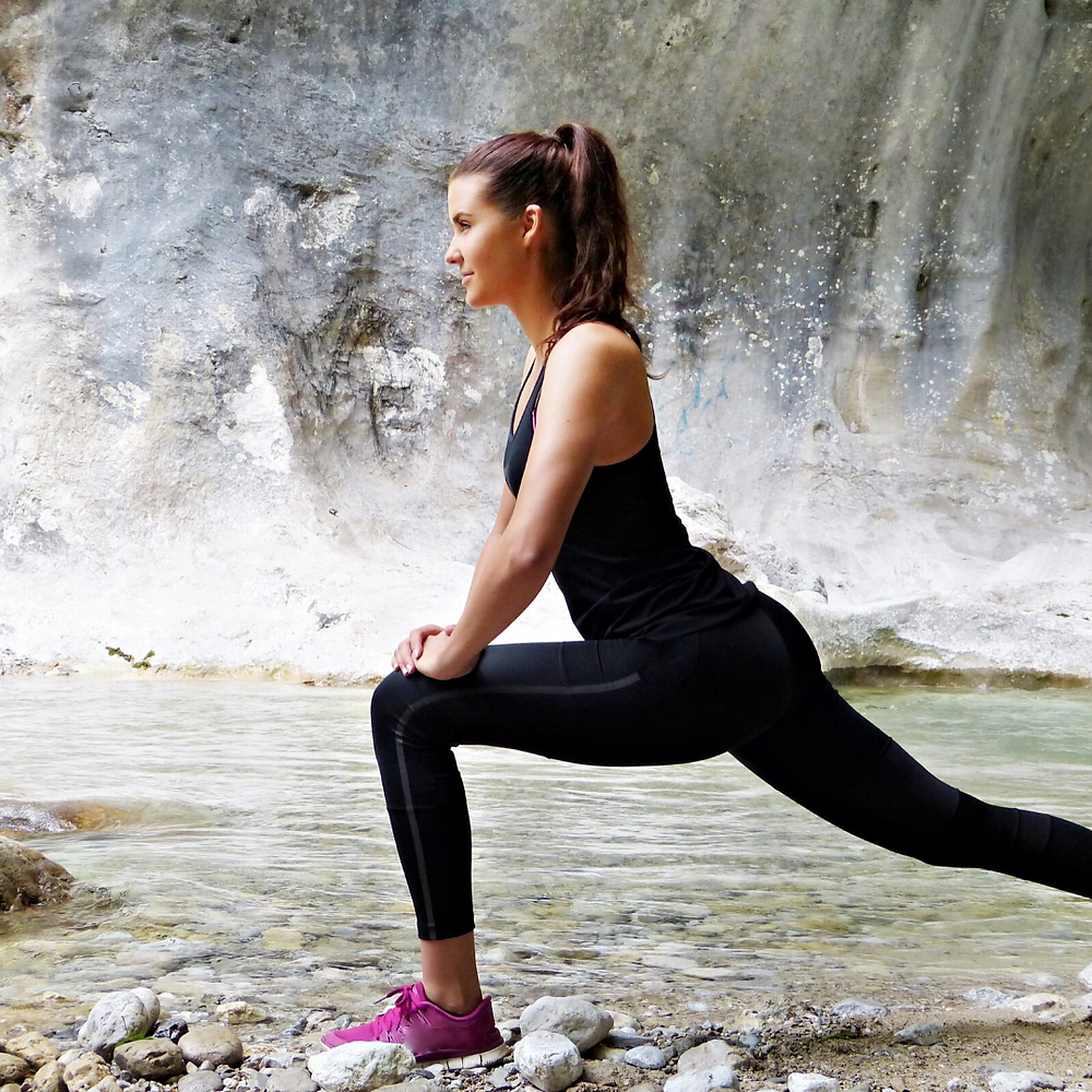 A women stretching in front of rocks and water