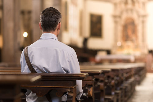 Man sitting in a pew at Church and medit