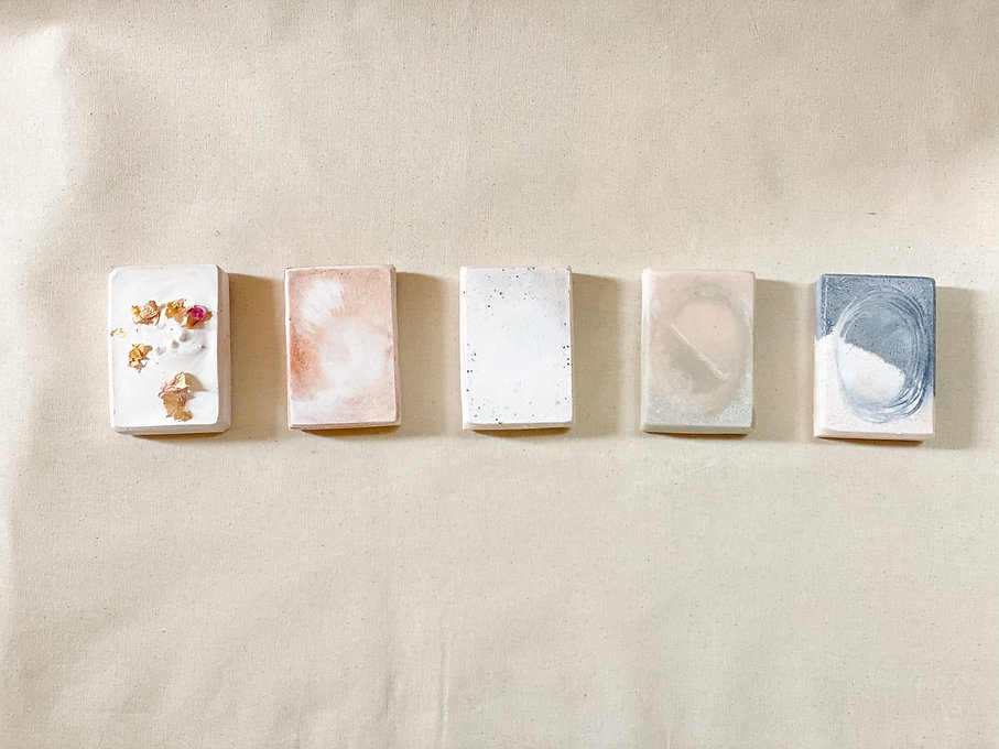 five colourful soap bars on a neutral cotton background