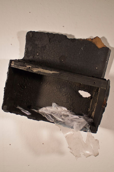 Thisis a sculpture hanging on a wall. It si a wood box that has been burned to black with some clear silicon and white feathers in it.