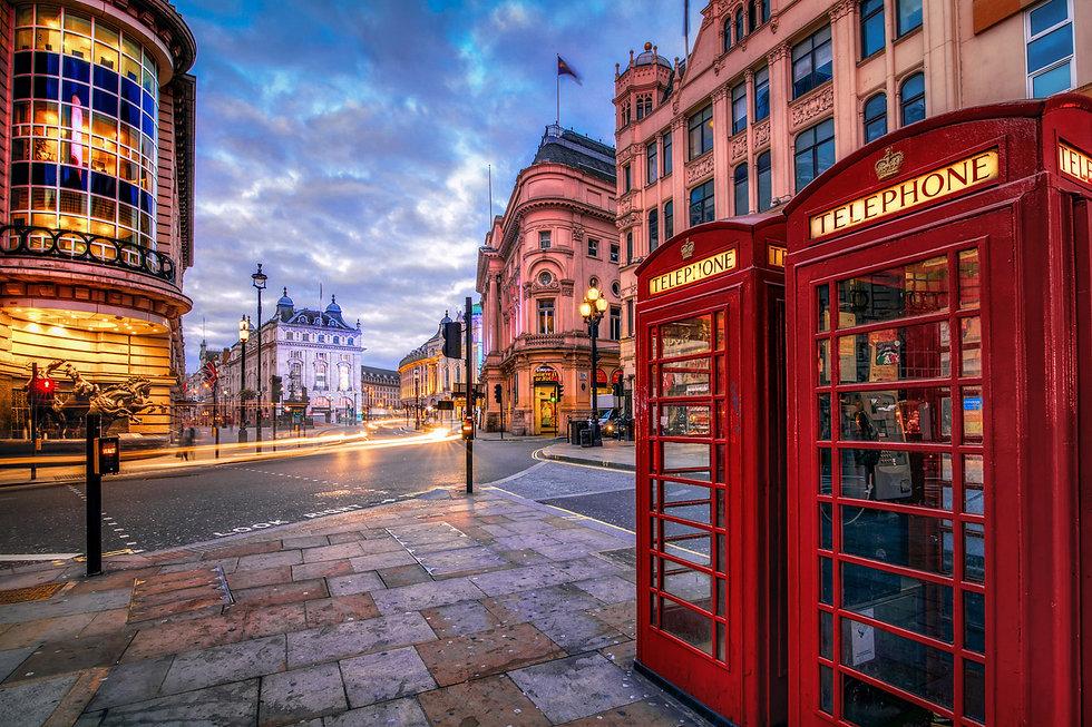 На картинке улочки Англии, с красной телефонной будкой, облачным небом и извилистой дорогой