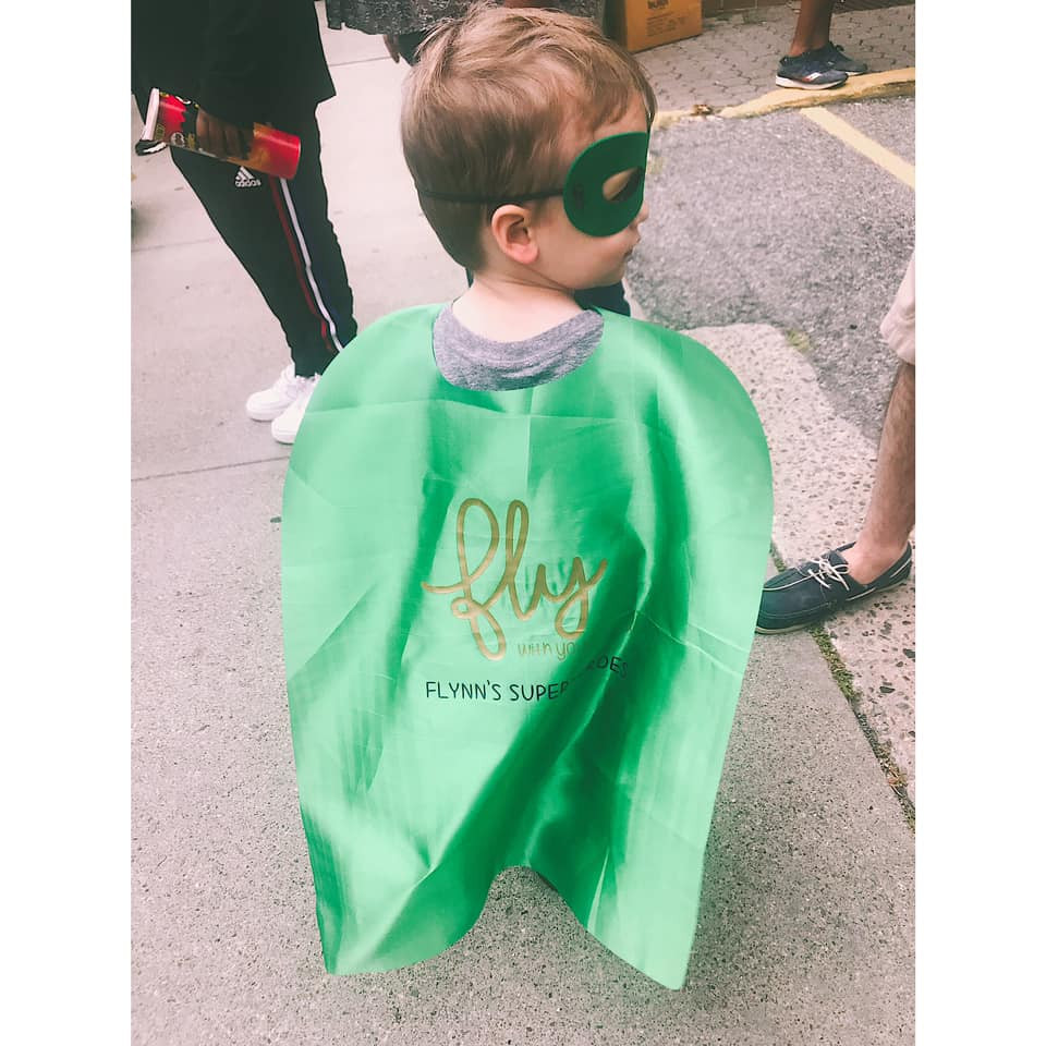 "Flynn wearing his green ""Fly With Your Own Wings"" cape, leading his team."