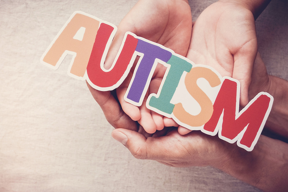 Image of hands holding a colorful sticker that spells out Autism.