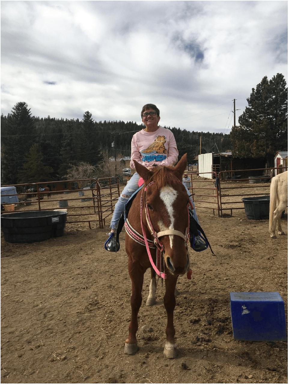 Donna Vroman montando a caballo durante su tiempo libre.