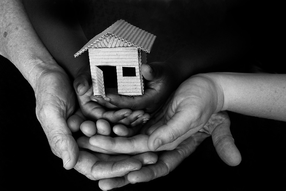 Hands holding a house made from cardboard