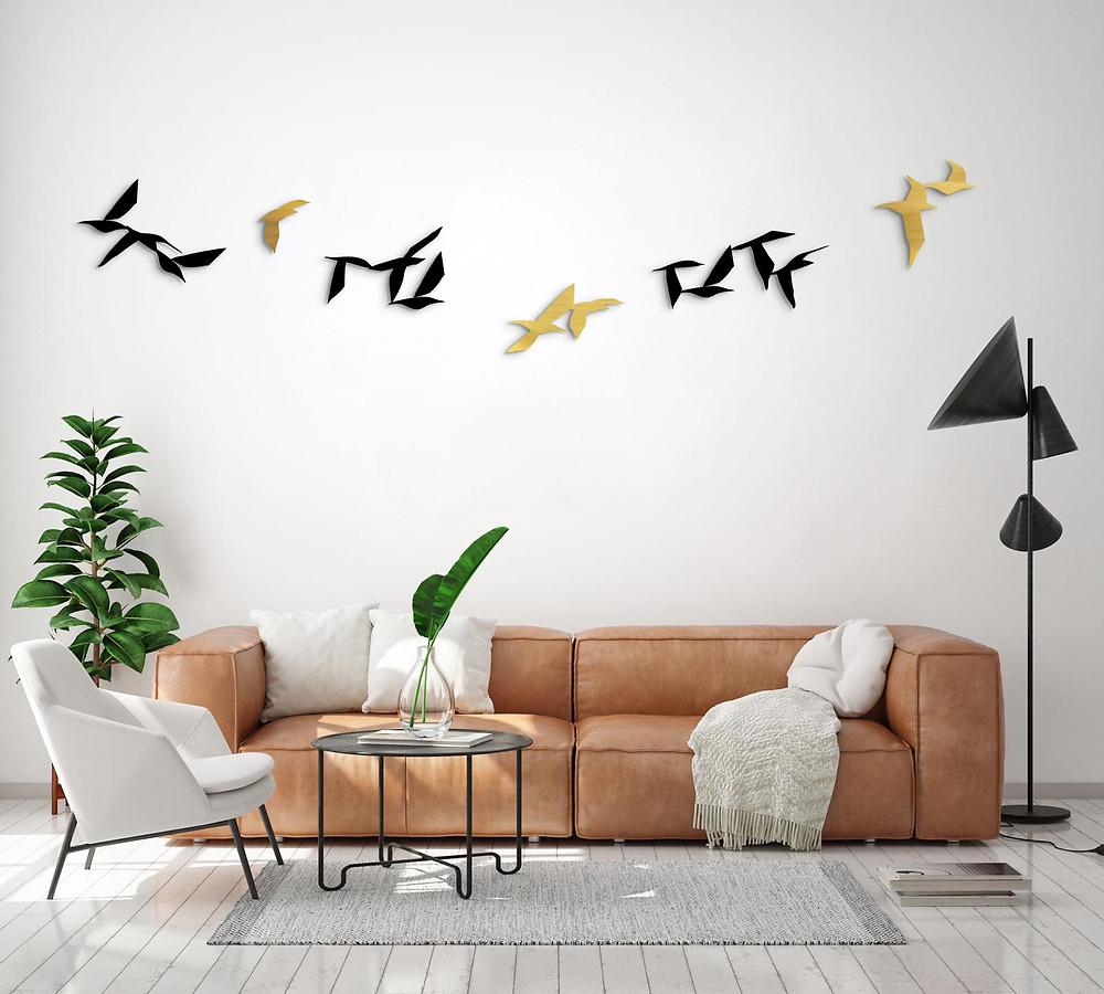 ציפורי מתכת תלויים על קיר סלון מעל ספה