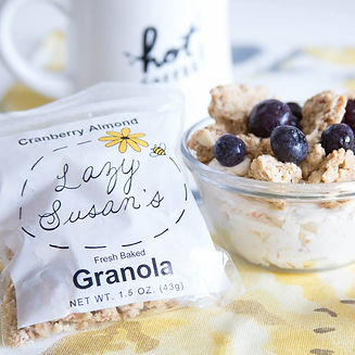 A mini bag of granola beside a bowl of granola with blueberries and yogurt.