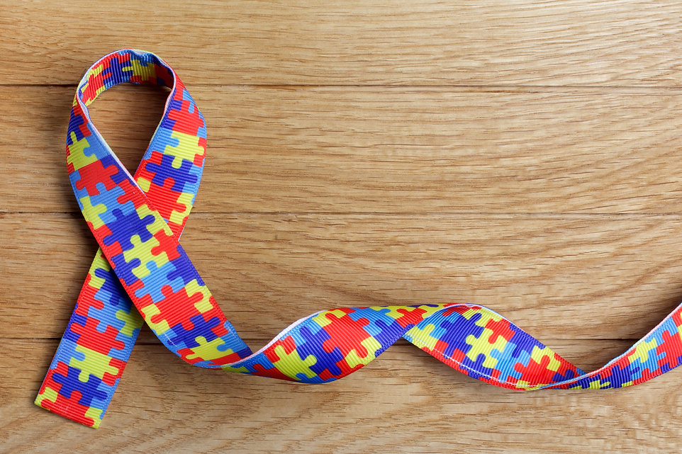 World Autism awareness and pride day or month with Puzzle pattern ribbon on wooden backgro