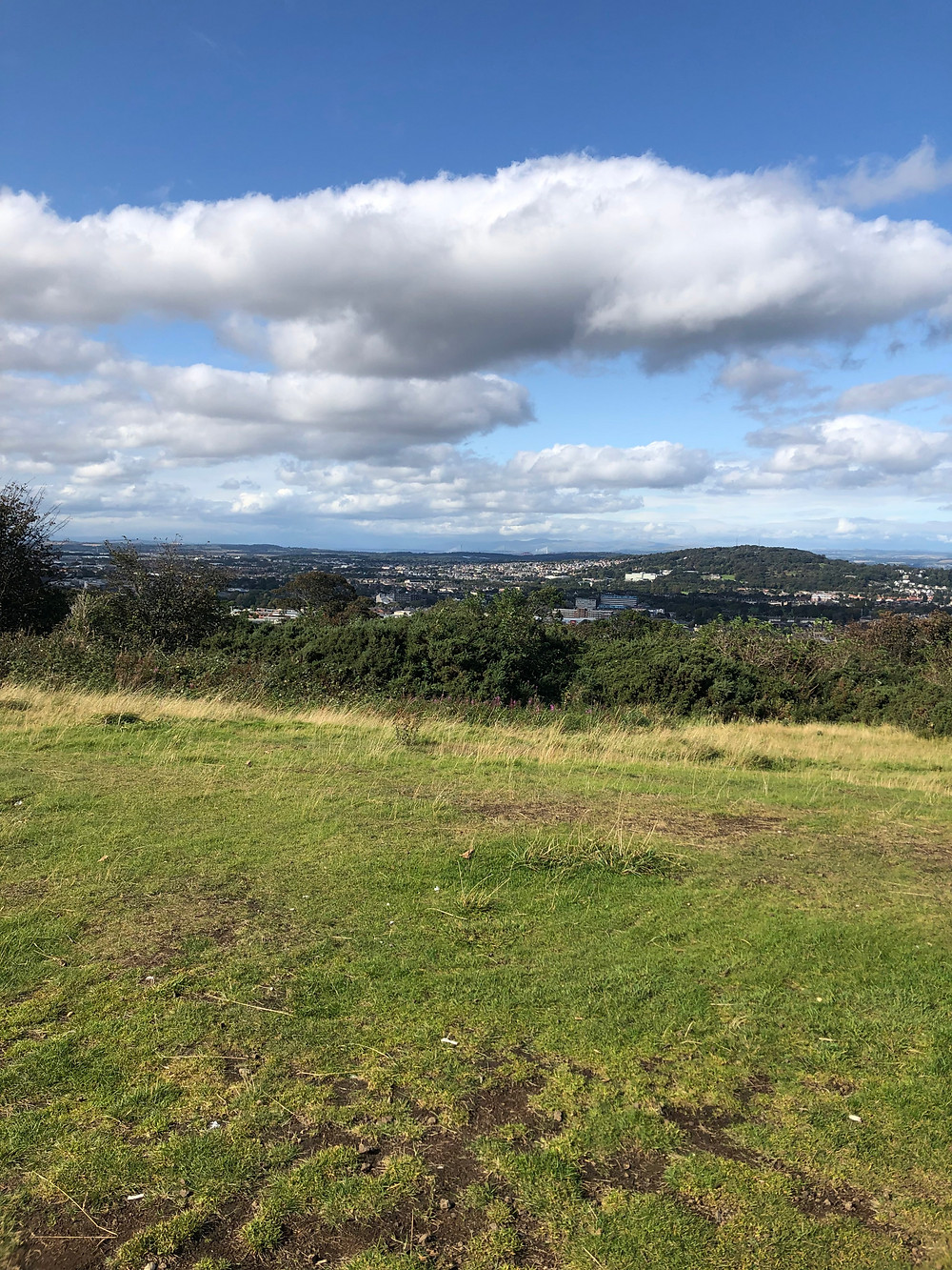 A view from the top of a grassy hill, looking over the Firth of Forth