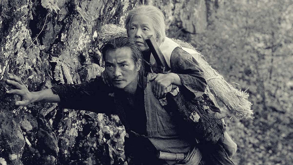 Iconic image from the Japanese film The Ballad of Narayama (1983). It shows a son carrying his mother in the mountain.