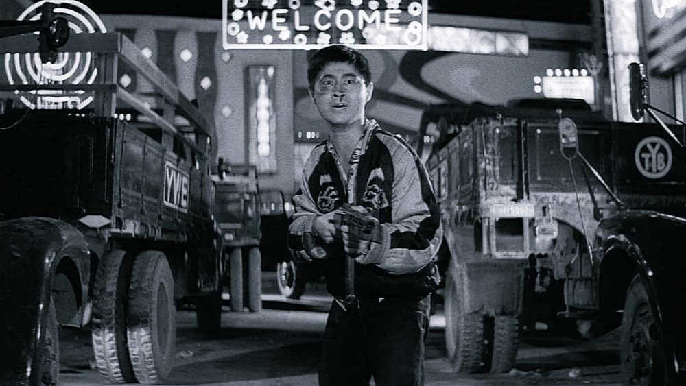 A Japanese thug stands with a machine gun in hand. From the film «Pigs and Battleships» (1961).