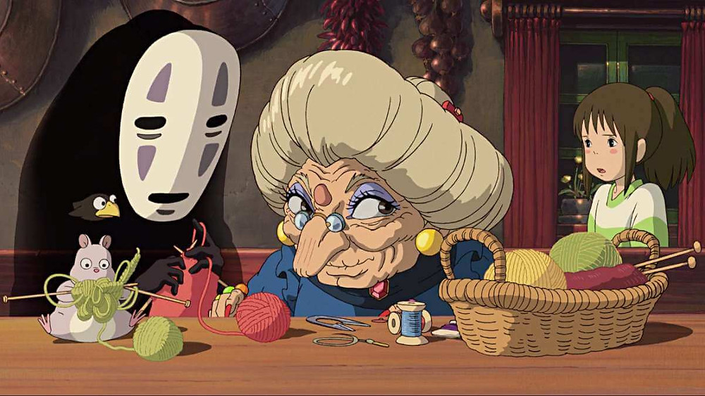 Chihiro looking confused when the witch, No-Face and the mouse are knitting. Taken from the anime film Spirited Away.