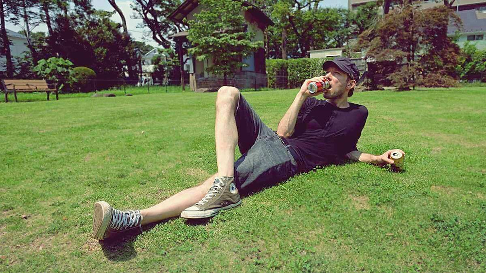 A relaxed guy lays on the grass in a Tokyo park and enjoys a few beers.