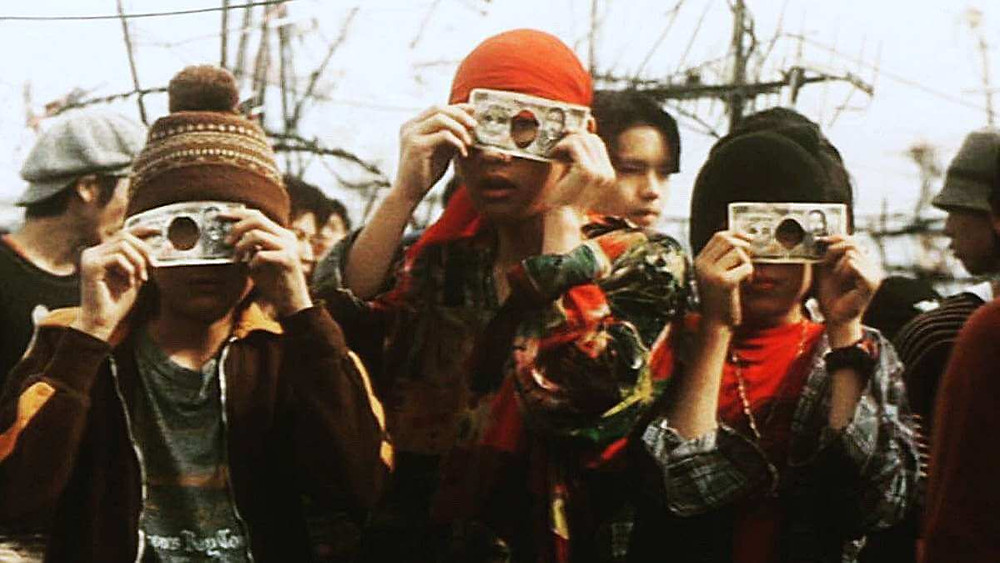 Three lower class kids playing with counterfeit money. Taken from the movie Swallowtail Butterfly (1996).