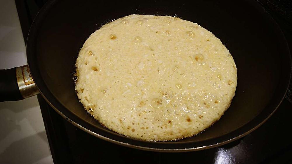 Okonomiyaki in a frying pan, the surface is full of bubbles.