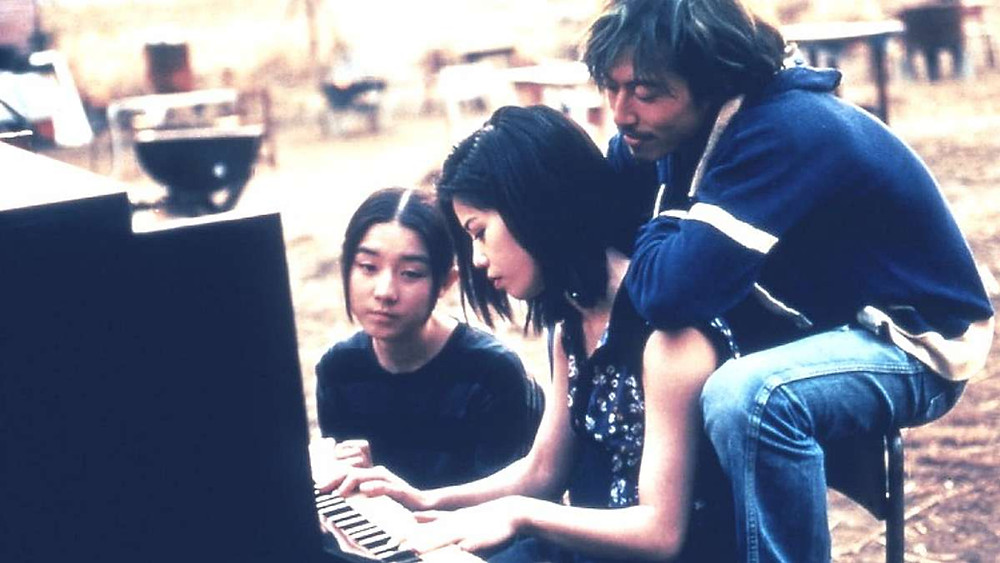 The three main characters in the movie Swallowtail Butterfly (1996) sitting around a piano. The scene look melancholic.