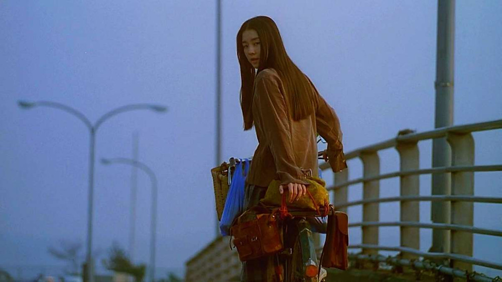 Ageha from the movie Swallowtail Butterfly (1996) is riding her bike while looking over her shoulder.