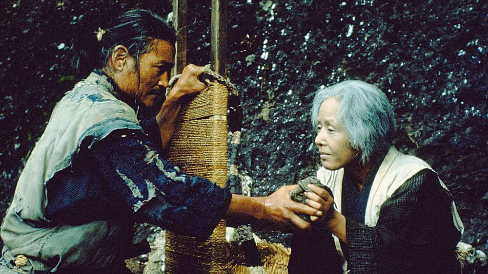 A son giving his mother a small food bag. Two protagonists in the Japanese film The Ballad of Narayama (1983).