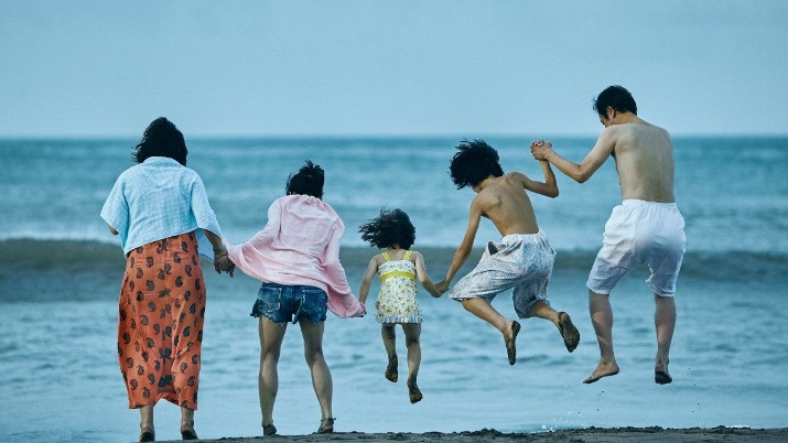 Family of five jumping from the waves on the beach. Taken from the Japanese film «Shoplifters» by Hirokazu Kore-eda.