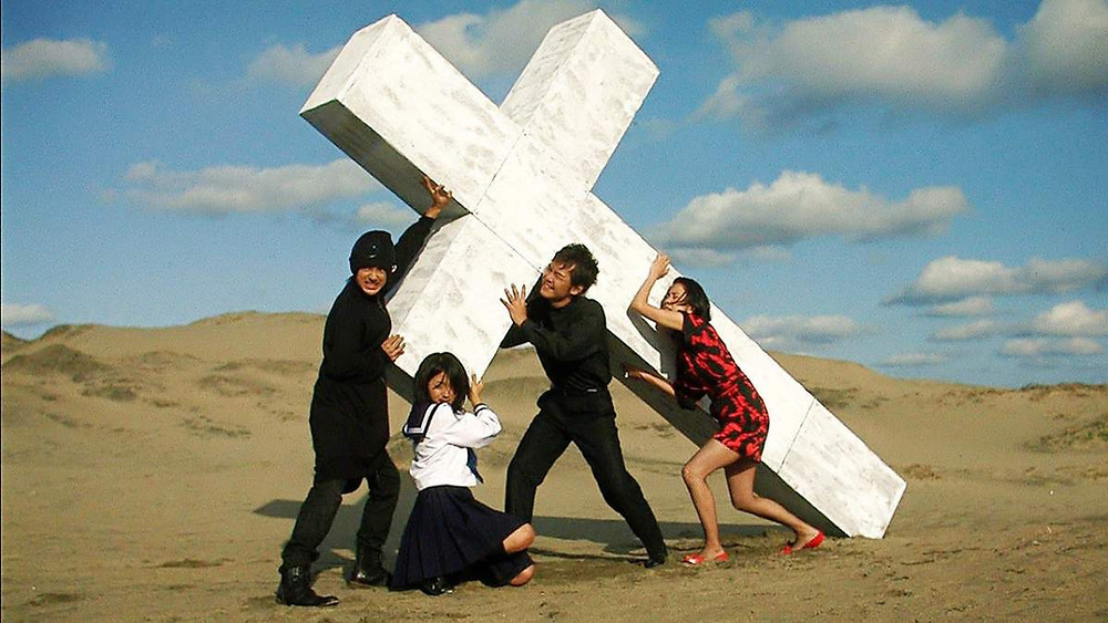Four characters carrying a giant crucifix in the movie Love Exposure by Sion Sono