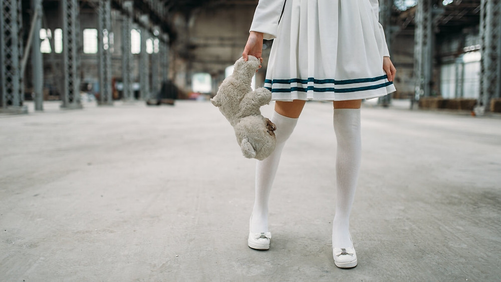 Kawaii Japanese girl in cosplay outfit standing on a factory floor, holding a teddy bear